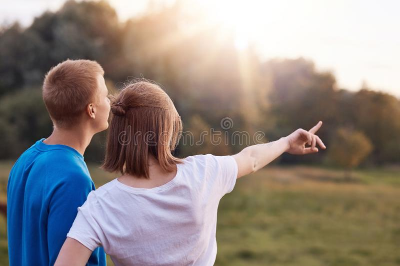 Back view of affectionate young couple stand closely, admire nature, see something into distance, enjoy sunset, copy space aside. royalty free stock photo