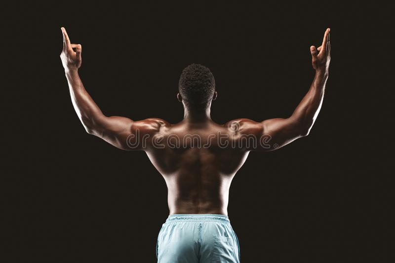 Back view of african bodybuilder raising his hands up stock images