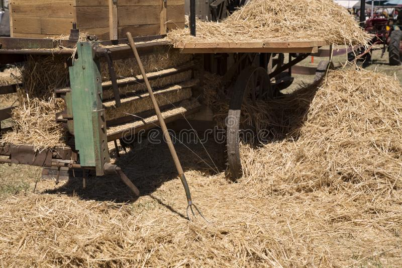 Back View Antique Hay Bailer, Pitch Fork, and Hay, Partial Soft Focus View of Tractor in Background royalty free stock image