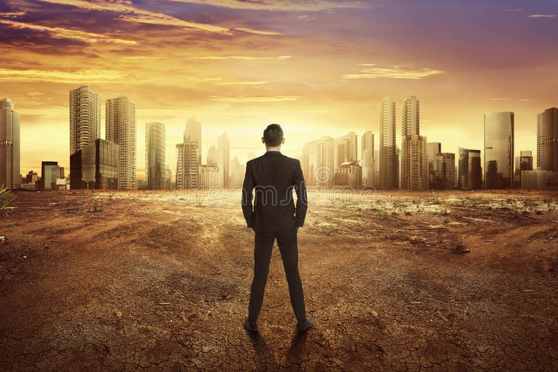 Back view asian businessman looking dry land effect of the climate change. From modern city royalty free stock photo