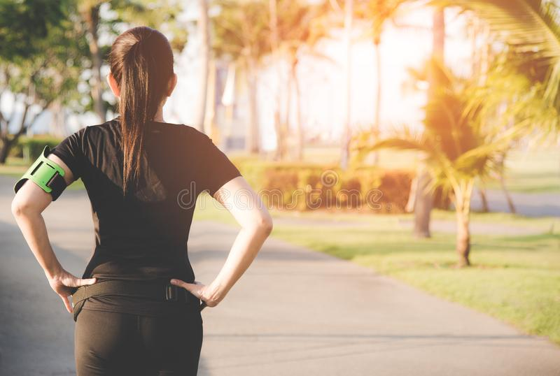 Back view of asian fitness woman standing before running on the outdoor workout in the park evening time. Sport and Healthy Concept stock image
