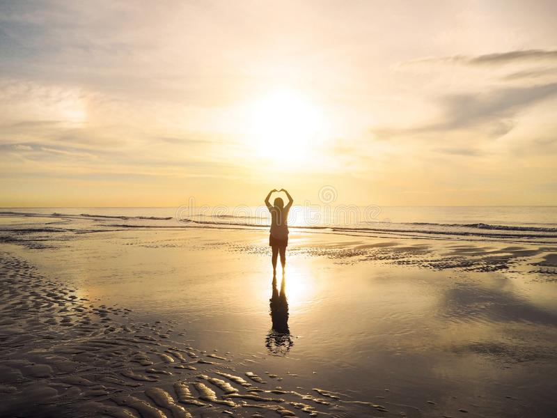 Back view Asian woman raised arms on air as heart shape at sunset sea royalty free stock photos