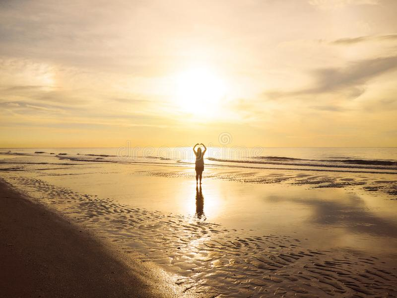 Back view Asian woman raised arms on air as heart shape at sunset sea stock photography