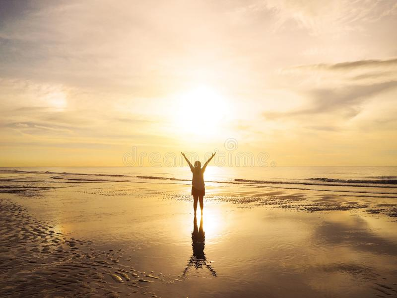 Back view Asian woman raised arms on air at sunset sea royalty free stock photography