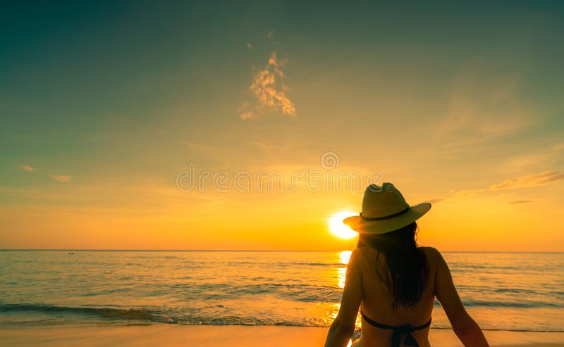 Back view of Asian woman wear bikini and straw hat sit on sand beach relax and enjoy holiday at tropical paradise beach. Woman stock photos