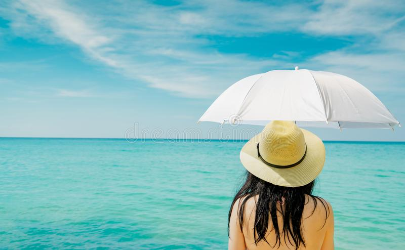 Back view of Asian woman wear swimsuit and hand hold white umbrella at tropical beach on sunny day with beautiful blue sky royalty free stock photos