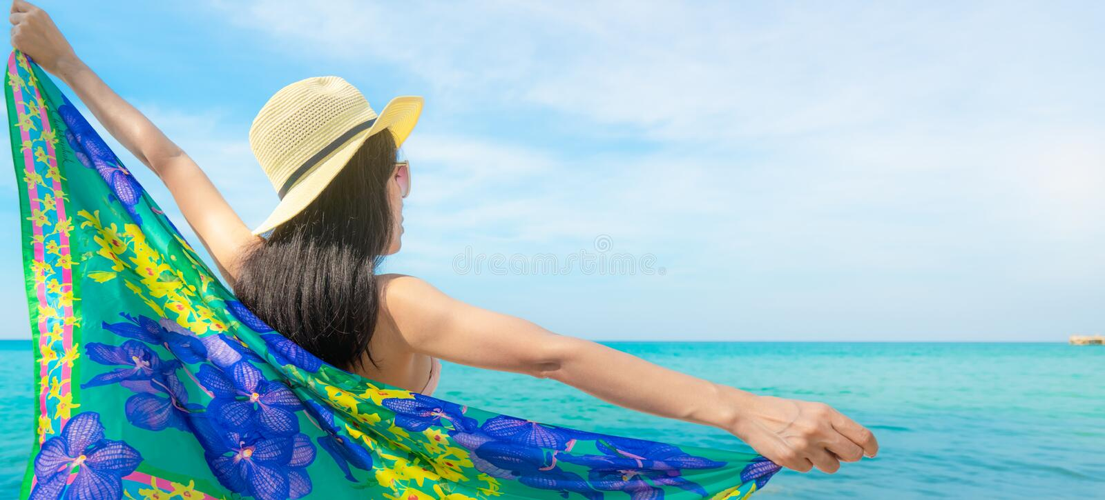 Back view of Asian woman wear swimsuit and opened arms at tropical beach on sunny day with beautiful blue sky and white clouds. Woman travel on summer vacation royalty free stock photography