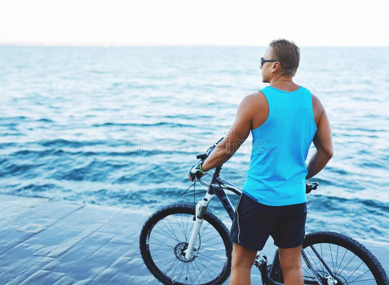 Back view of athletic sexy man with bicycle outdoors at seaside. stock photo