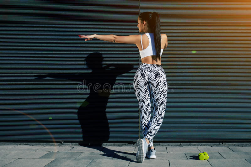 Back view athletic woman with perfect figure and buttocks shape exercising against wall with copy space for your text message stock photo