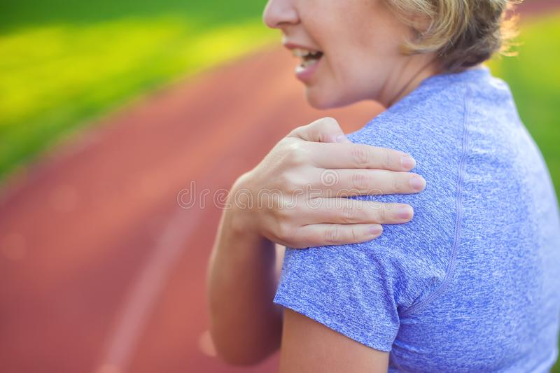 Back view of athletic young woman in sportswear touching her painful neck at the stadium. Sport, health and people concept. Back view of athletic young woman in stock image