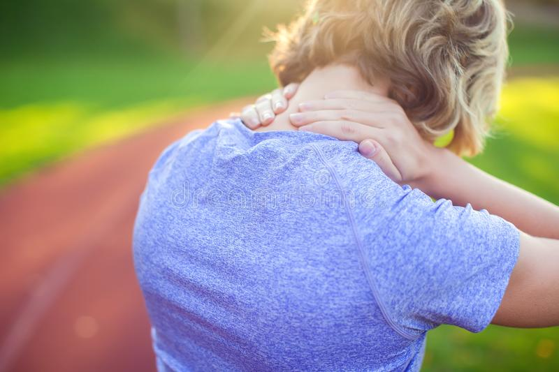 Back view of athletic young woman in sportswear touching her painful neck at the stadium. Sport, health and people concept. Back view of athletic young woman in royalty free stock images