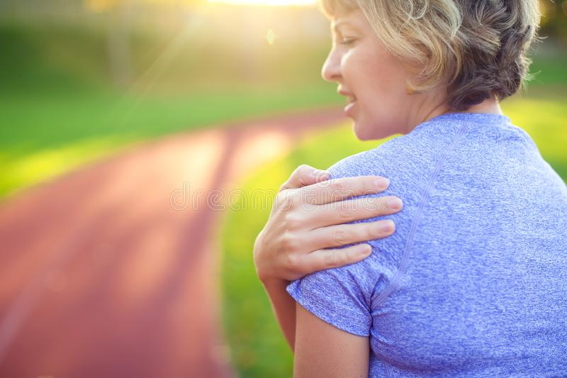 Back view of athletic young woman in sportswear touching her painful neck at the stadium. Sport, health and people concept royalty free stock photo