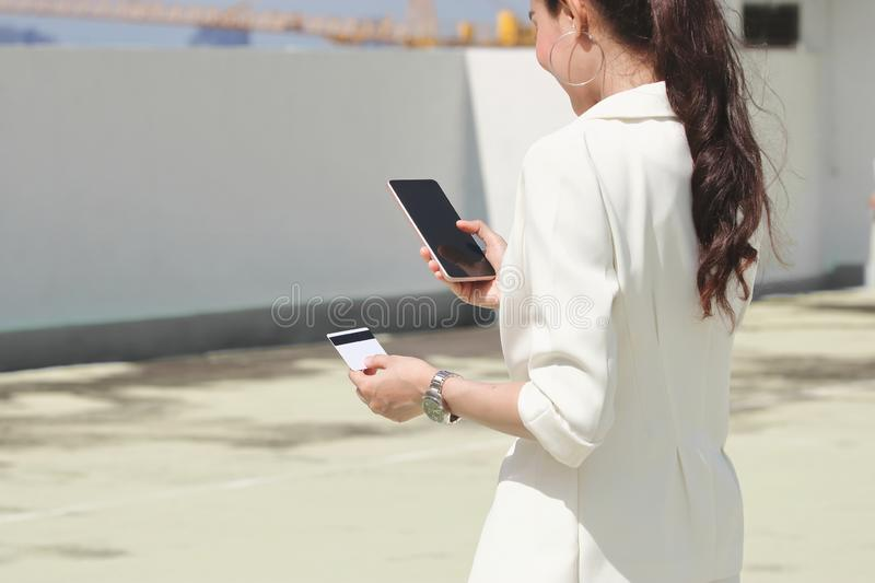 Back view of attractive young Asian woman with mobile smart phone and credit card for shopping online.  stock images