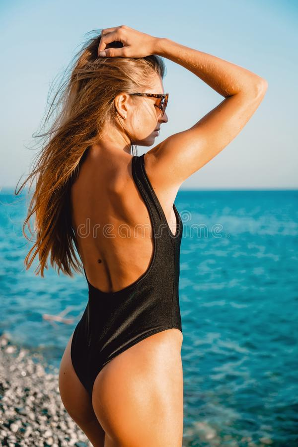 Back view with attractive young woman in bikini relaxing at sea stock photos
