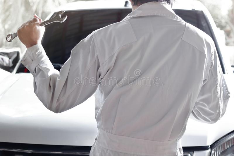 Back view of automotive mechanic in uniform with wrench diagnosing engine at the repair garage. Insurance car concept. Back view of automotive mechanic in royalty free stock photos