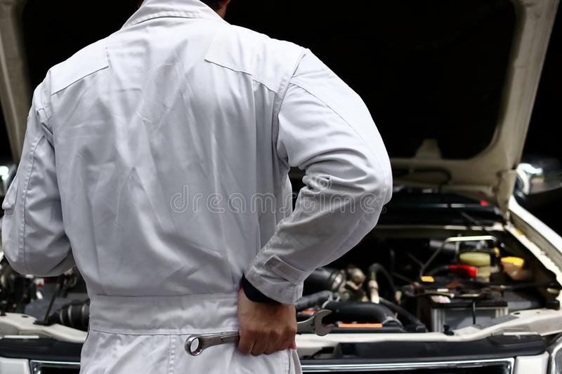 Back view of automotive mechanic in white uniform with wrench diagnosing engine under hood at the repair garage. Car insurance co. Ncept royalty free stock photo