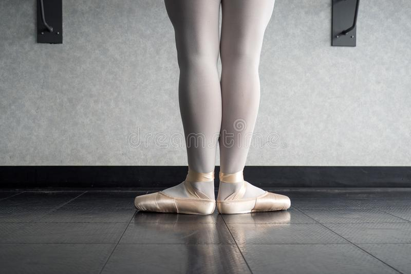 Back view of ballet dancer ballerina at the barre in dance class standing in first position stock images