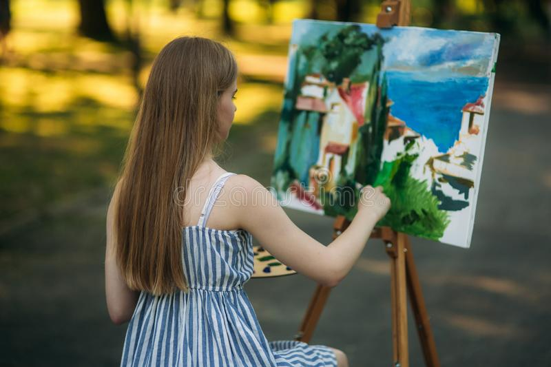 Back view of beautiful blond hair girl drawing a picture in the park.  royalty free stock photo
