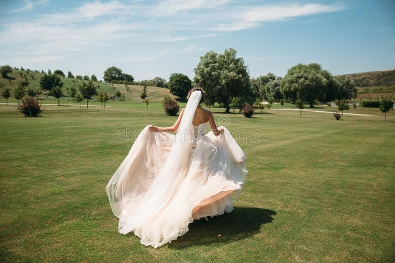 Back view, beautiful bride in luxury fashion white wedding dress with veil on the green golf club glade, wedding day. Amazing full length body portrait of girl royalty free stock photography