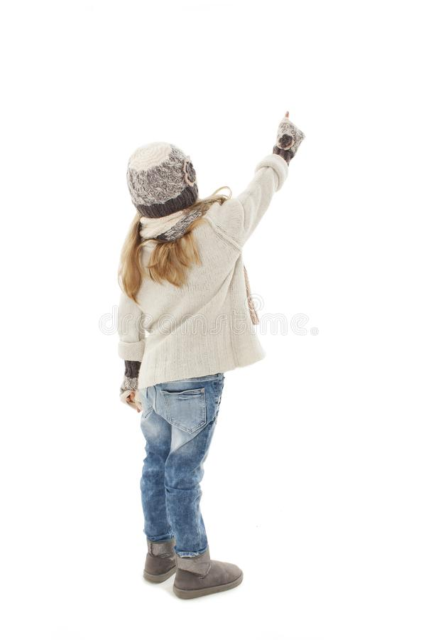 Back view of beautiful caucasian blonde fashionable girl in warm clothes pointing up. Winter style. royalty free stock photos
