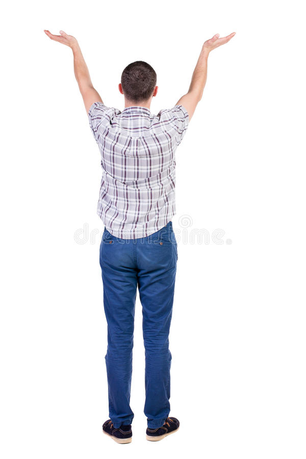 Back view of Beautiful man in jeans looking at wall and Holds h. And up. young brunette standing. Rear view people. Isolated over white background. The guy in a stock photos