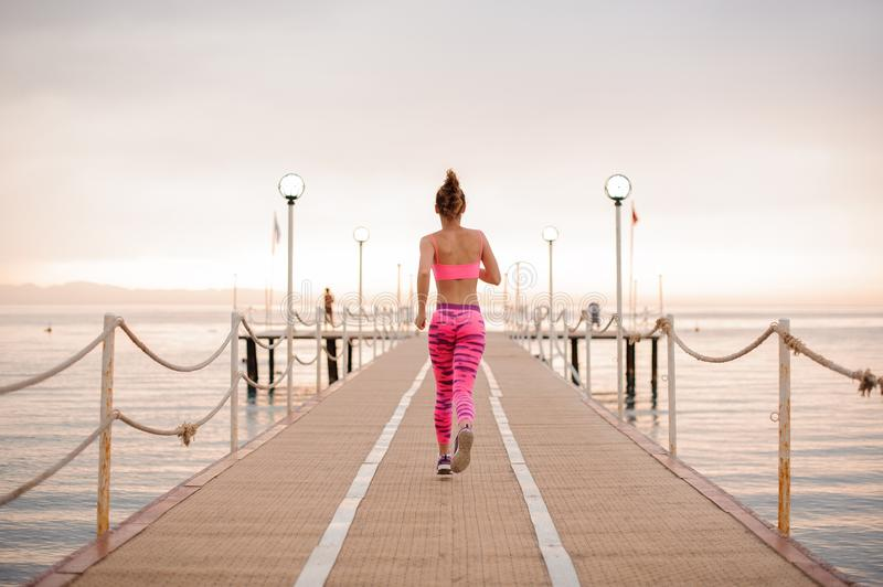 Back view of beautiful slim and young girl running over the wooden bridge royalty free stock photo