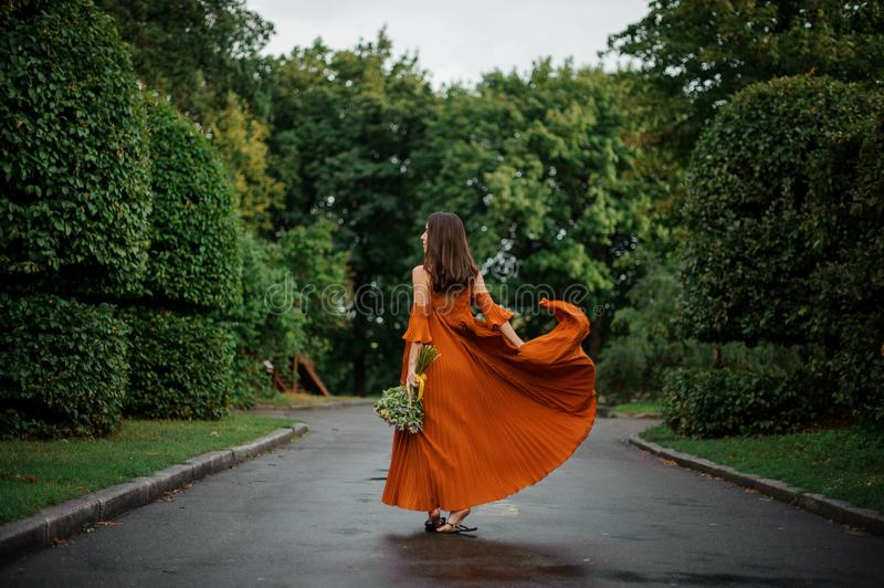 Back view of beautiful woman in long orange dress walking on the wet road royalty free stock image