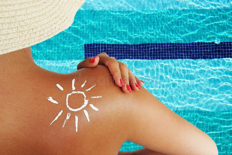 Back view of a beautiful woman taking care about her skin at swimming pool, sun protection concept stock photography