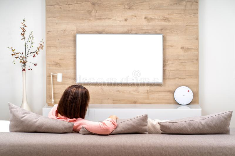Back view of beautiful young woman resting in luxury appartments, sitting on the sofa and watching TV. royalty free stock images