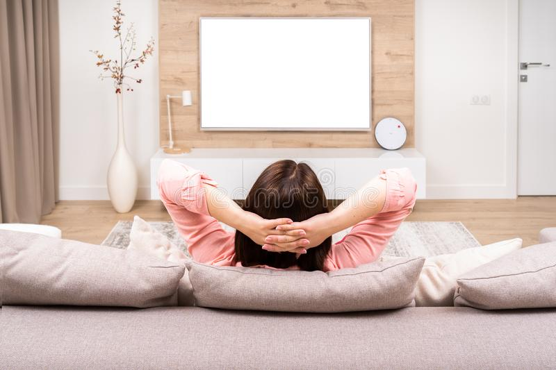 Back view of beautiful young woman resting in luxury appartments, sitting on the sofa and watching TV. stock photography