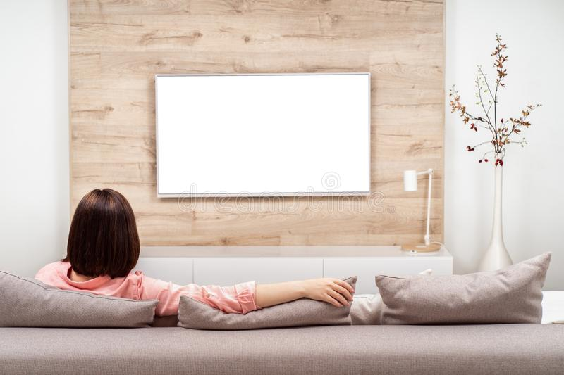 Back view of beautiful young woman resting in luxury appartments, sitting on the sofa and watching TV. Blank screen stock image
