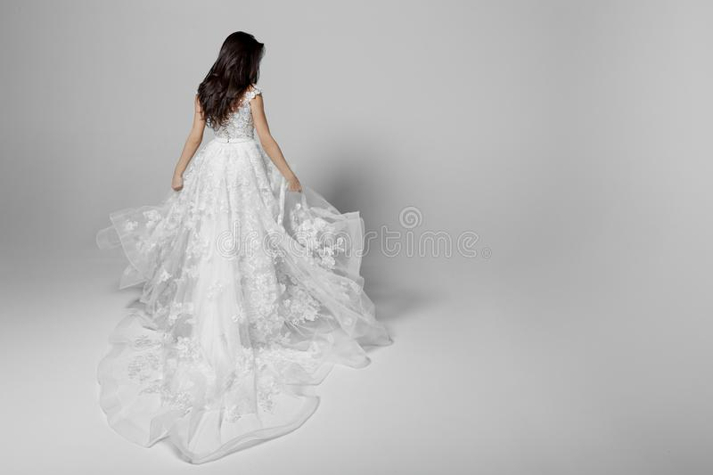 Back view of a beautiful young woman in wedding flying white princess dress, isolated on a white background. Copy space. stock image
