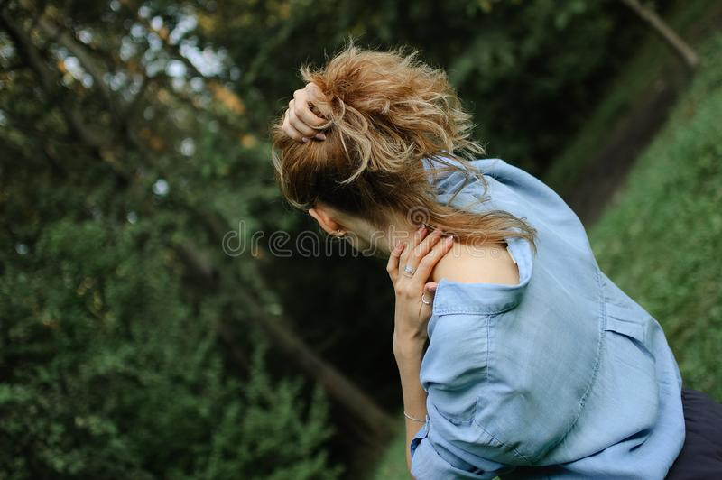 Back view of blonde adult woman wearing blue casual jeans blouse posing in the park on green trees background. Hipster royalty free stock images