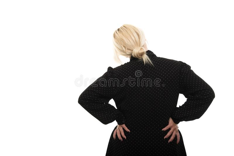 Back view of blonde female teacher showing back pain gesture stock photo