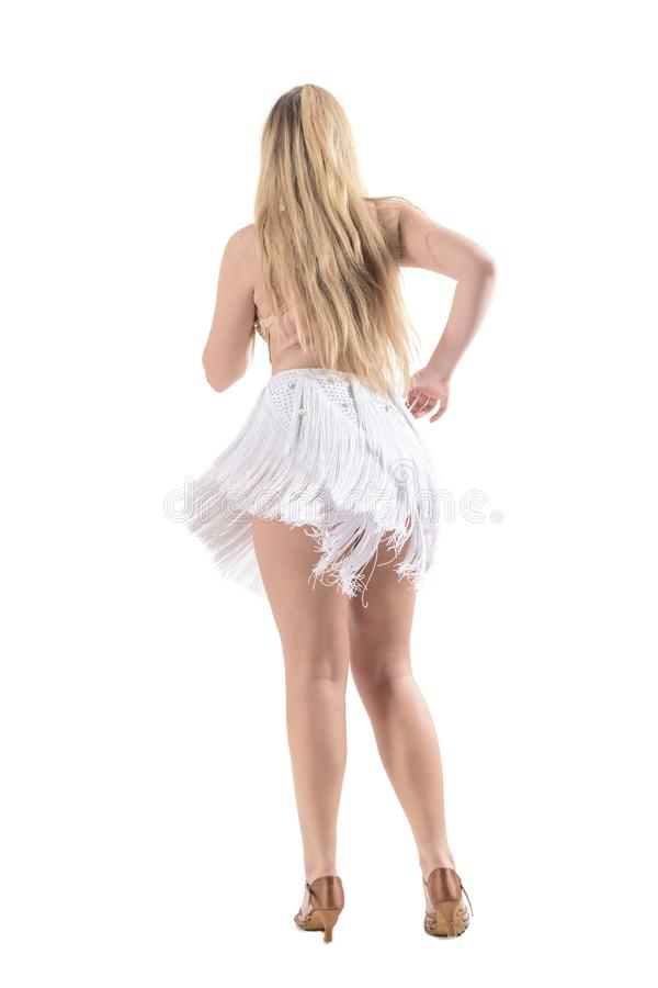 Back view of blonde woman dancing bachata wearing flowing fringed dress stock photos