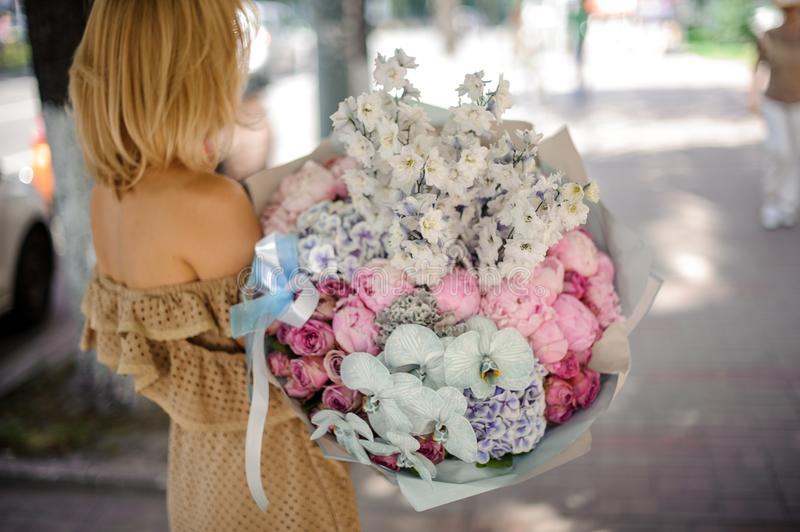 Back view of blonde woman holding a big bouquet of various flowers stock images