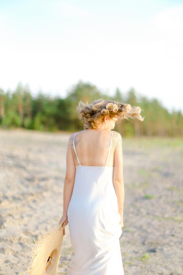 Back view of blonde woman walking on rocky beach with hant in hands and wearing dress. Back view of blonde girl walking on rocky beach with hant in hands and stock image