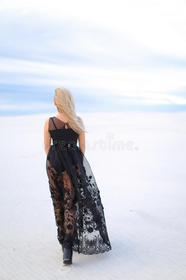Back view of blonde woman wearing black dress and walking in winter steppe. stock photos