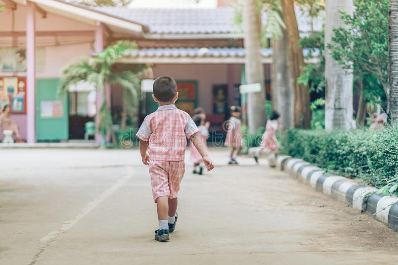 Back view of Boy followed girl friends on street to go to the classroom royalty free stock photography