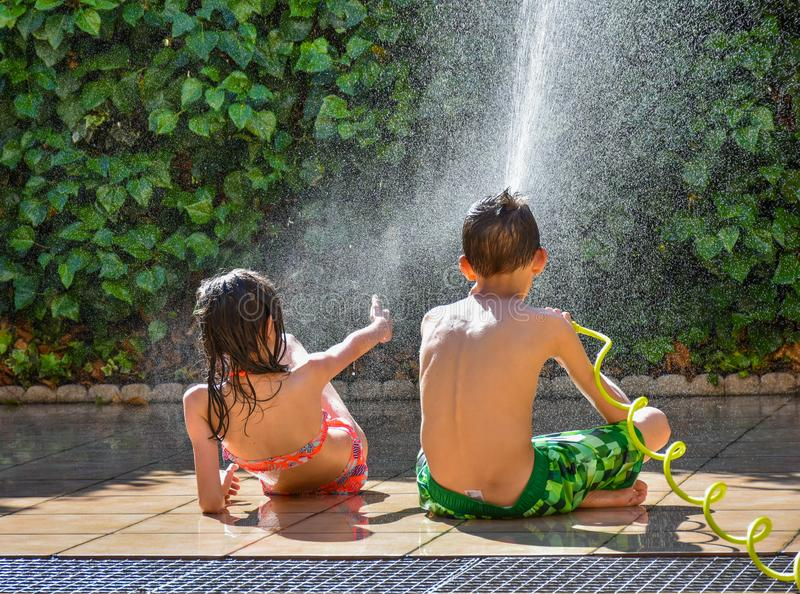 back view of a boy and a girl wearing swimsuit having a fun time of summer in a terrace of a garden playing with a hose refreshing stock photography
