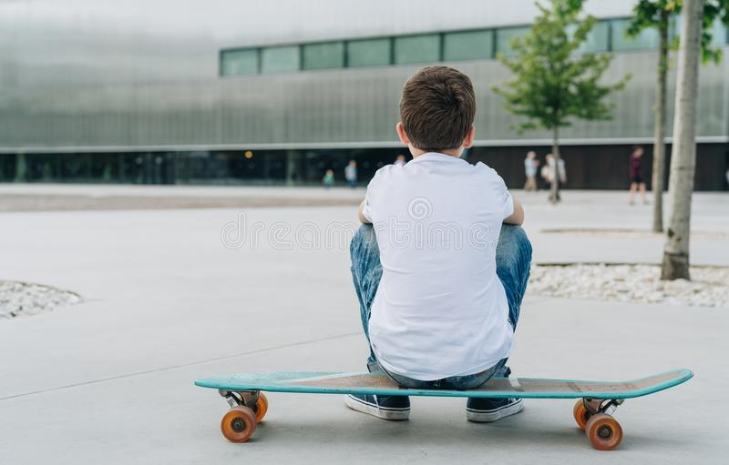 Back view. Boy in white T-shirt and blue jeans, sits on city street on skateboard. Space for text, logo, image. Mock up. Back view. The boy, dressed in a white stock image