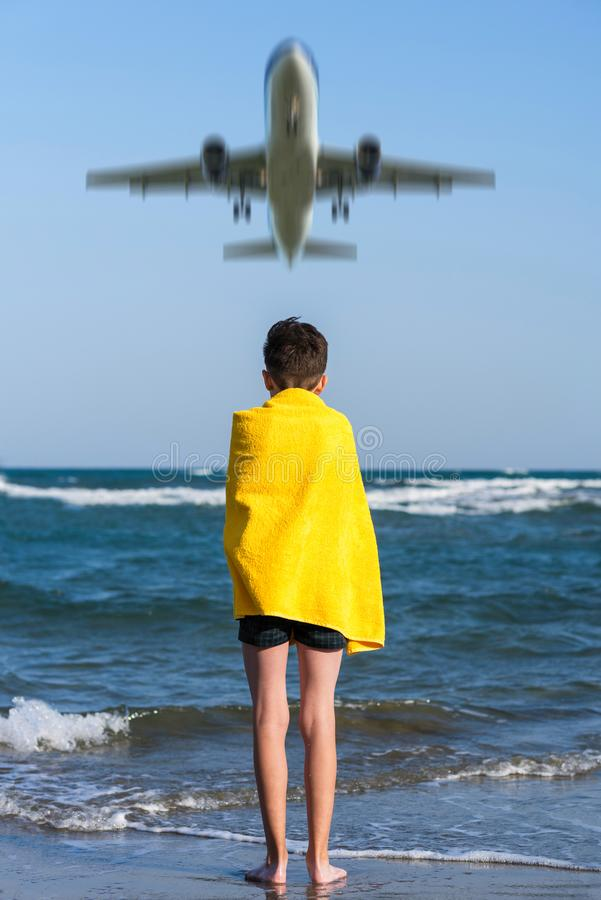 Back view on the boy in the yellow towel standing on seashore under landing plane. royalty free stock image
