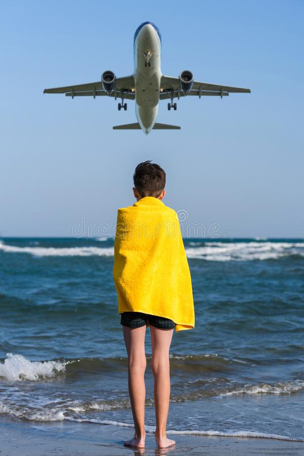 Back view on the boy in the yellow towel standing on seashore under landing plane. stock photos