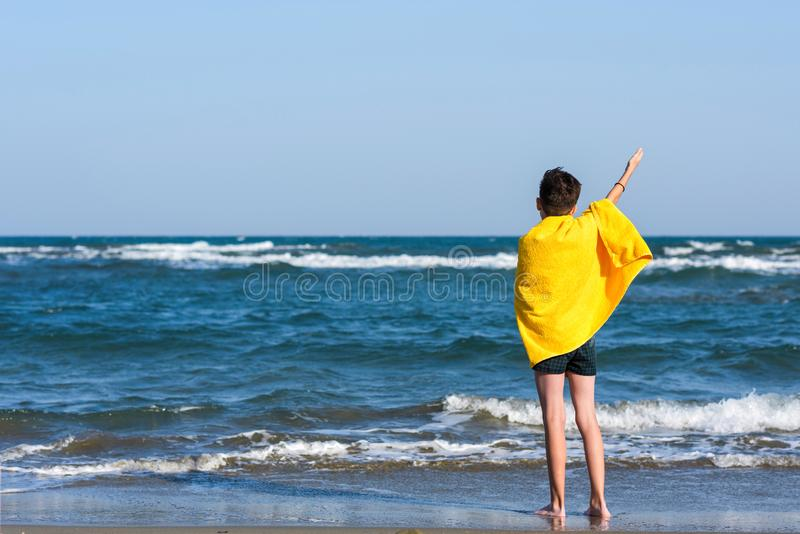 Back view on the boy in the yellow towel standing on seashore and waving his hand to landing plane. Travel Concept. royalty free stock image