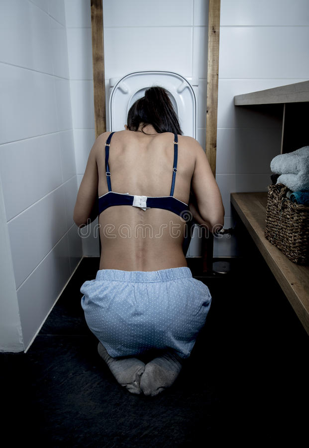 Back view of bulimic woman feeling sick vomiting and throwing up in WC toilet stock images