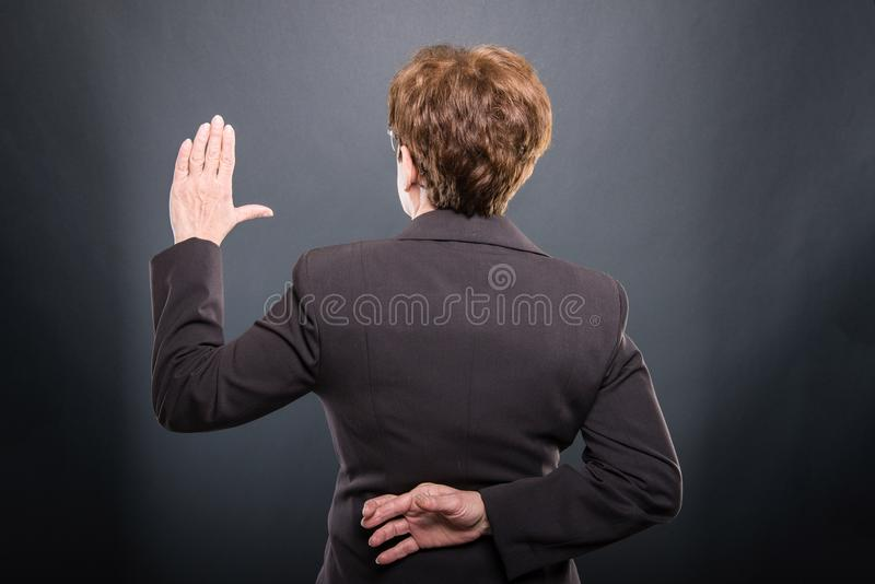 Back view of business senior lady taking fake oath royalty free stock images
