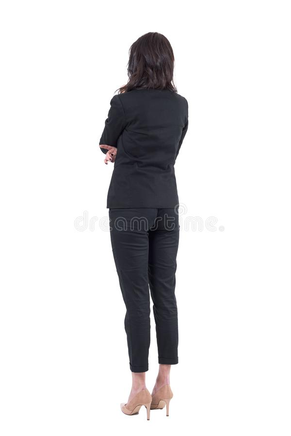 Back view of business woman in black suit with crossed arms watching interested. stock images