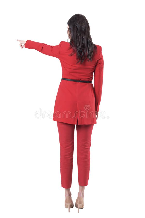 Back view of business woman leader in red suit pointing finger showing directions. Full body isolated on white background stock photo