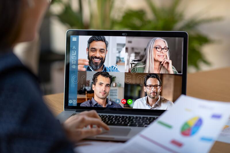 Smart working and video conference. Back view of business women talking to her colleagues about business plan in video conference. Multiethnic business team stock image
