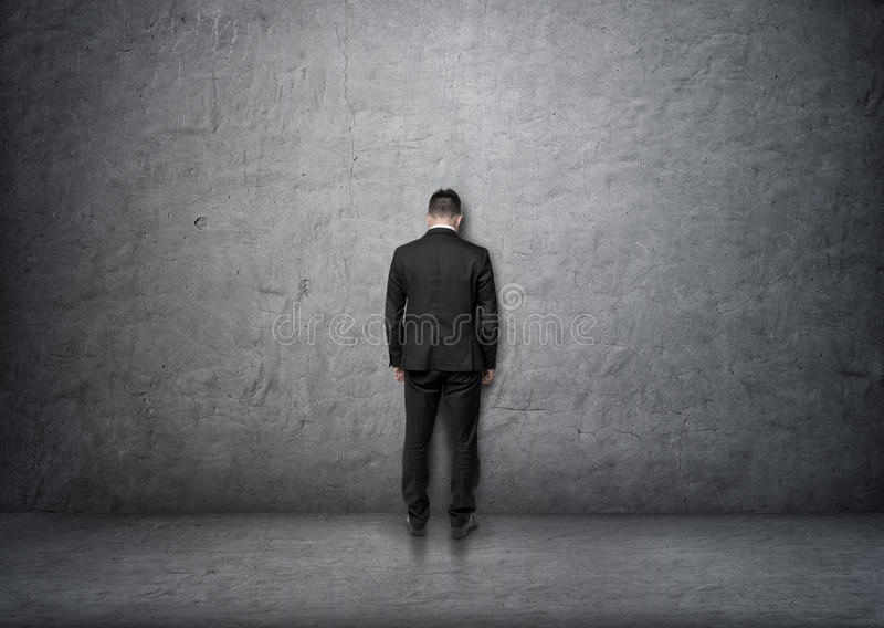 Back view businessman with bowed head standing in front of concrete wall royalty free stock photo